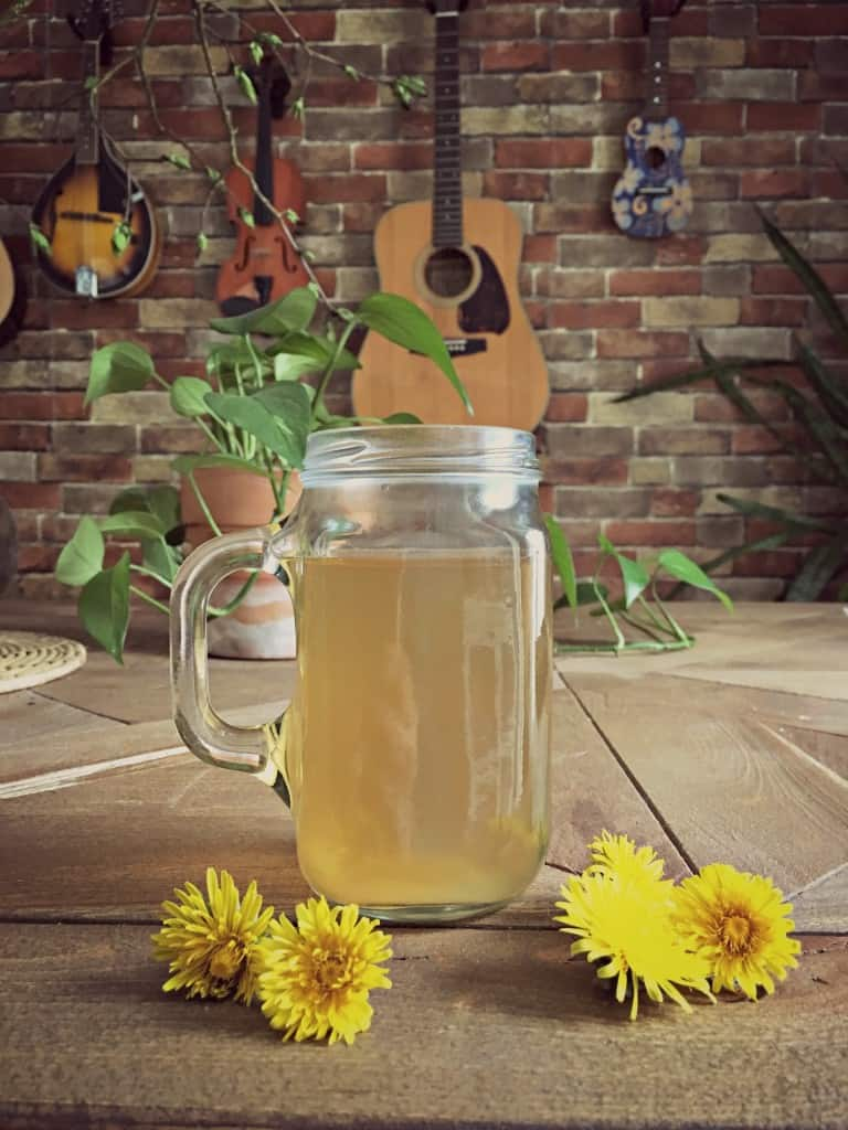 dandelion root tea in mug on table with dandelion flowers