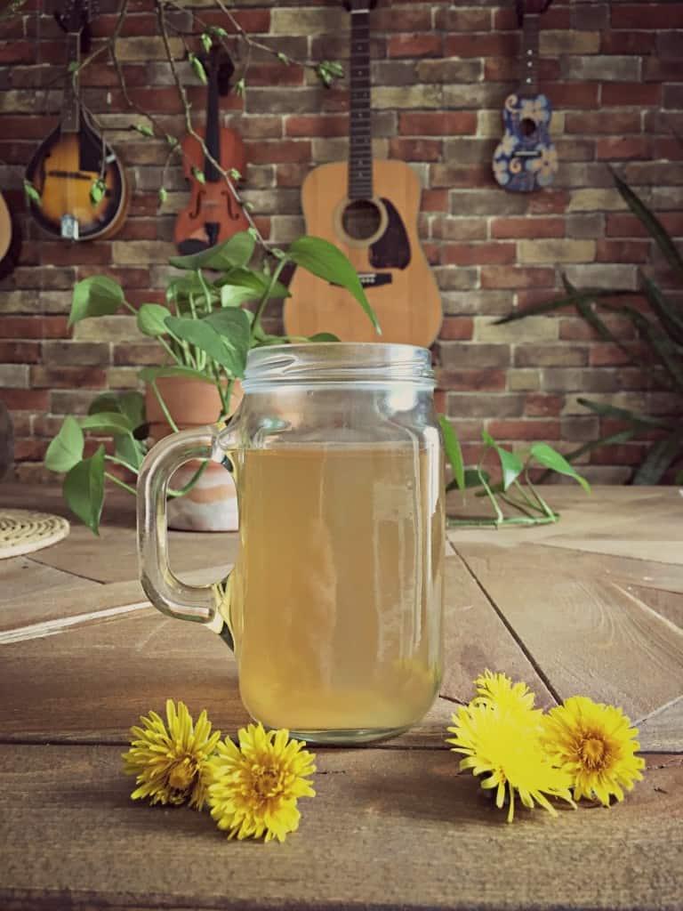 dandelion root tea in mug on table with dandelion flowers