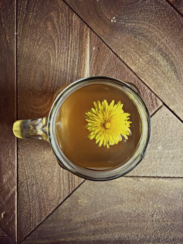 dandelion root tea in cup with yellow flower