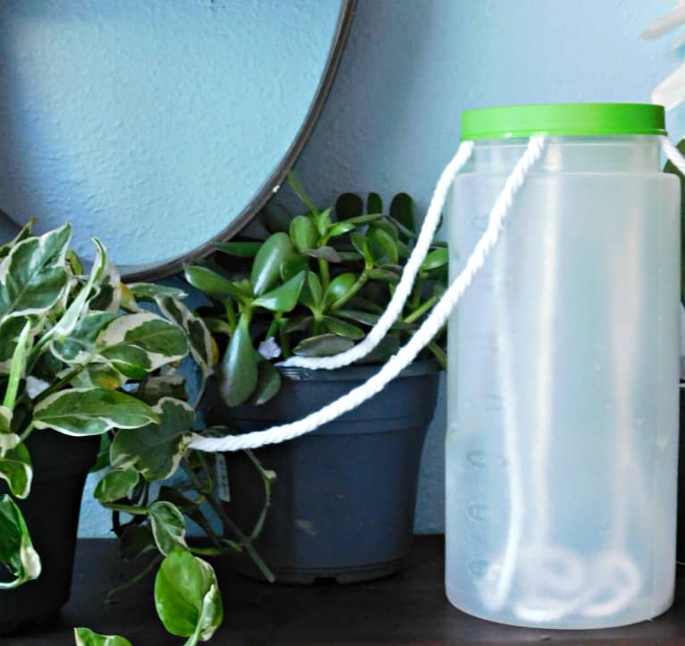 close up of jug of water with string wicking water to plants