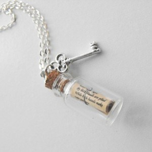Key and scroll necklace on white tabletop