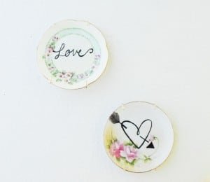 fun antique plates painted and hung up on the wall as decoration with the words love and a heart drawn on them