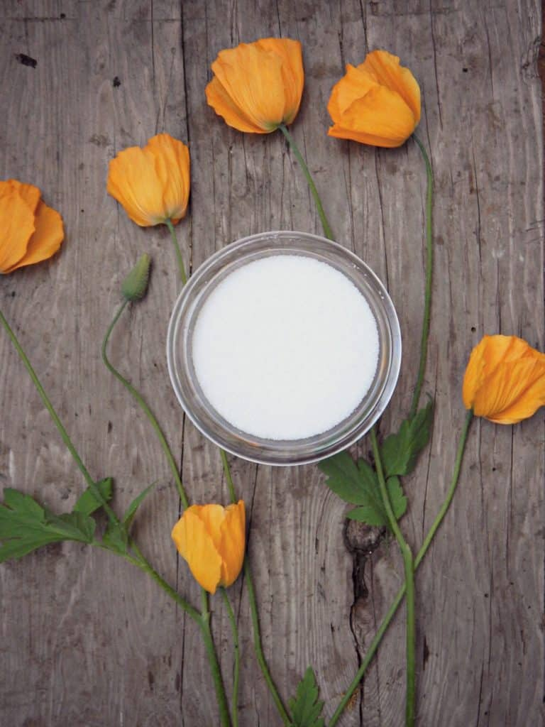 white sugar on wood table with orange flowers beside it