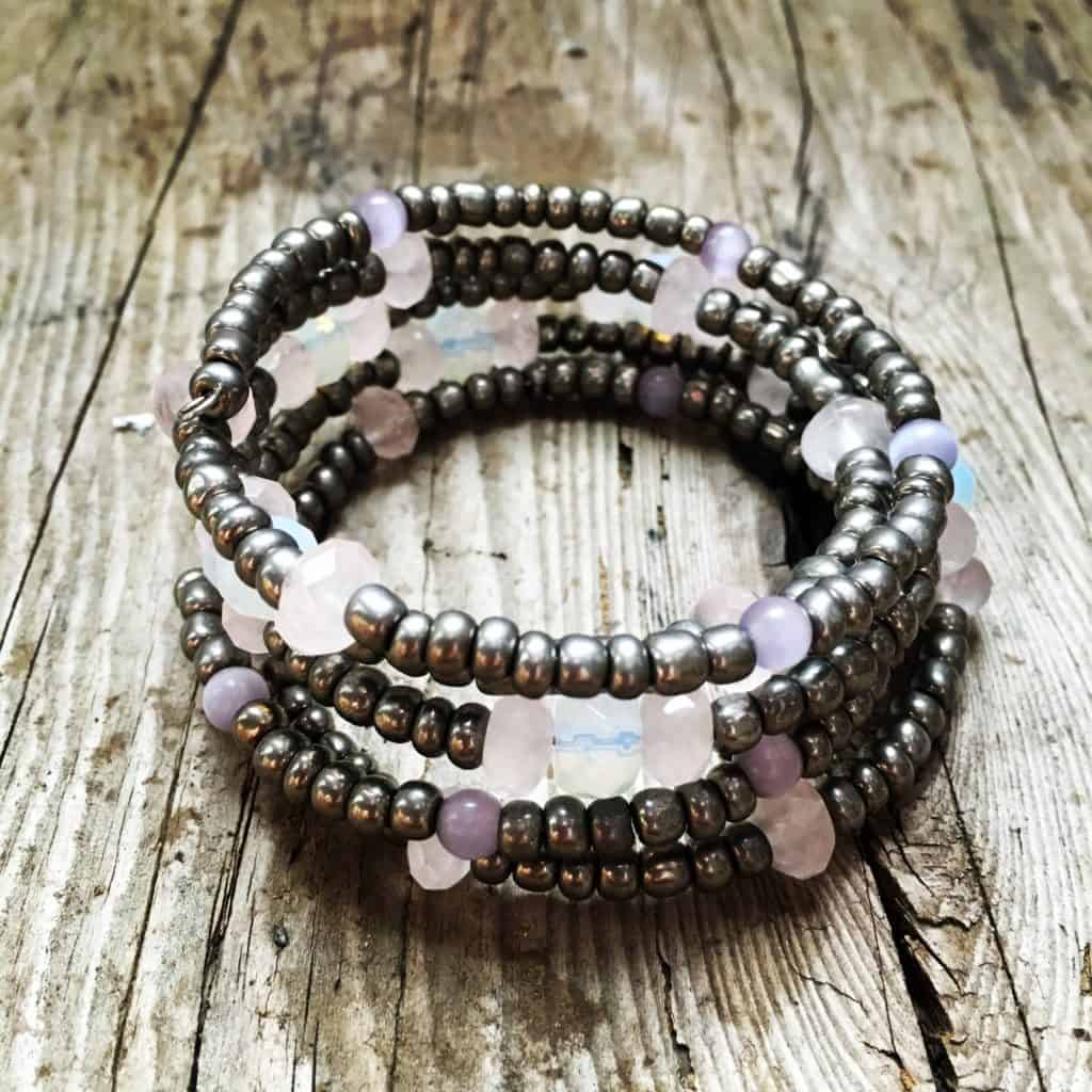 grey and pink beaded memory wire bracelet on wood table