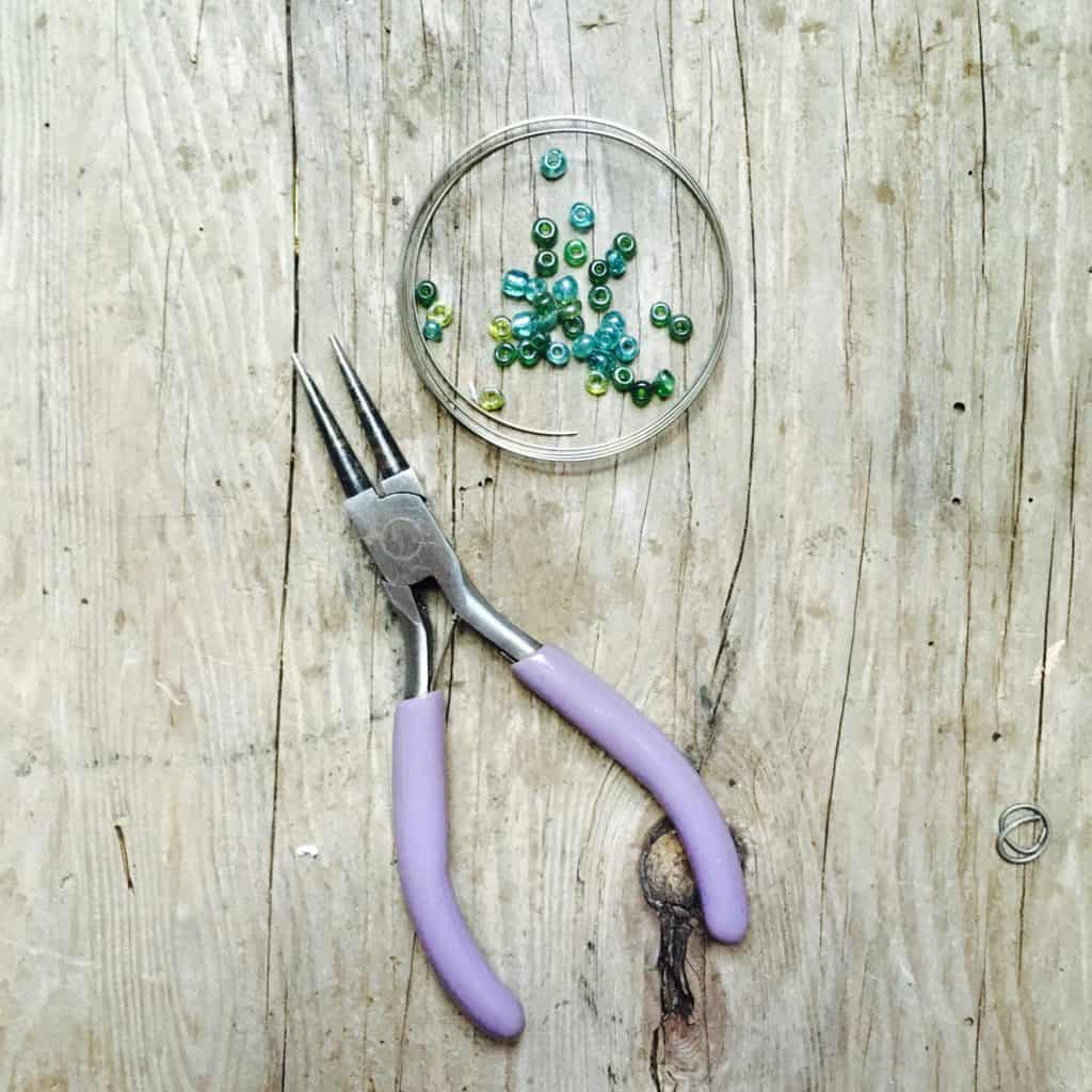 memory wire coiled, blue and green beads and needle nose pliers on wood table