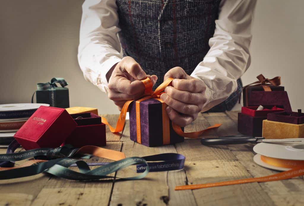 man wrapping box with bow