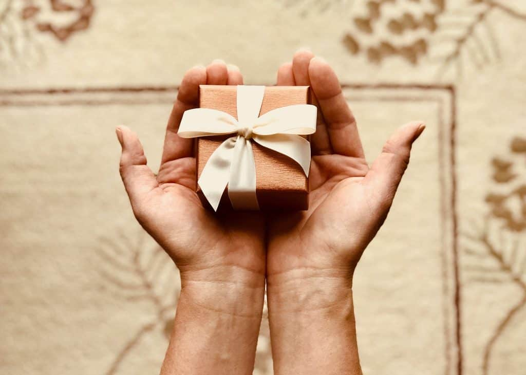 small box with bow held in hands