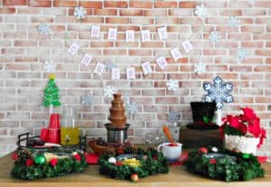 merry christmas banner on wall above table full of snacks