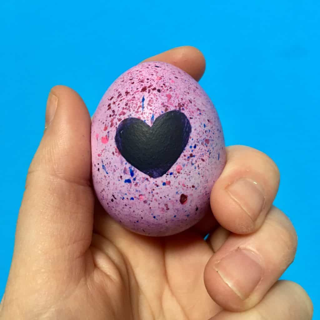 hatchimal egg being held by hand with blue wall in the background