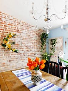 beautiful table with flowers on it and wreath on brick wall in the background