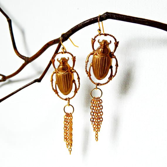 Gold beetle earrings with fringe hanging from branch