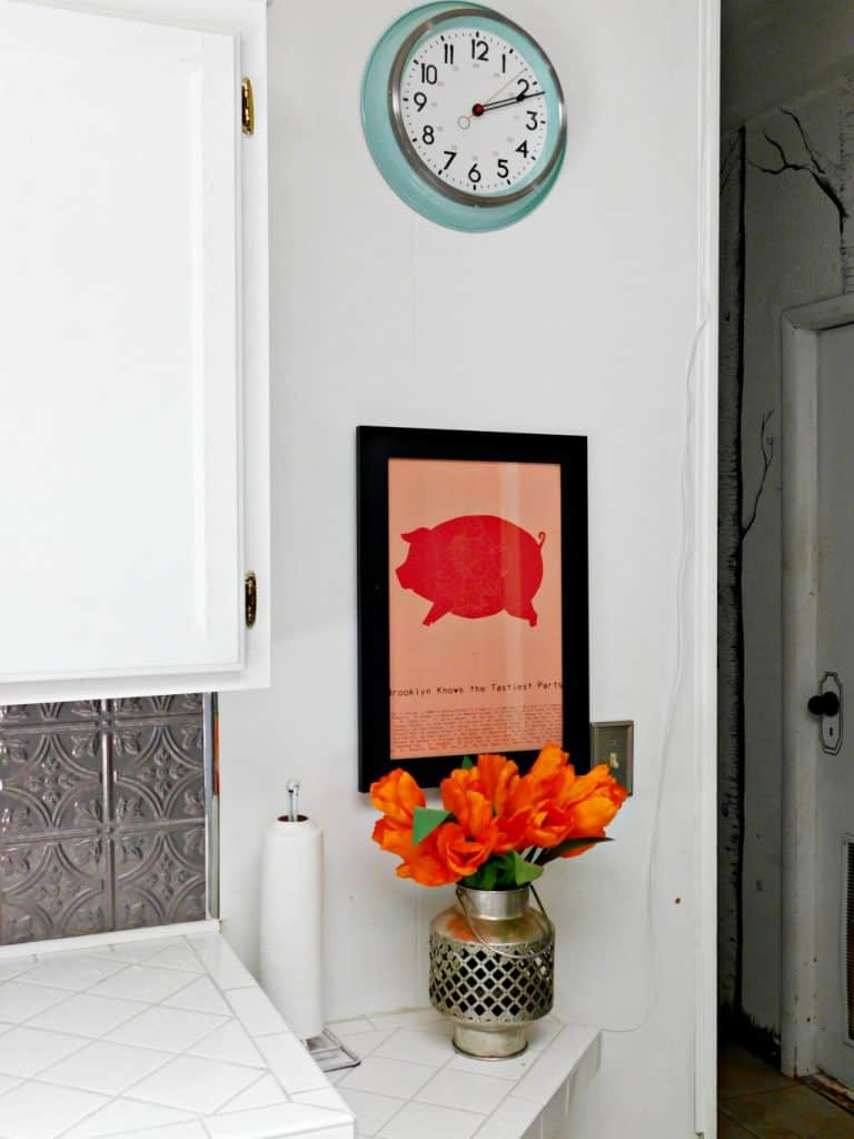 kitchen with green clock, pig picture and orange tulips