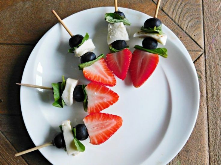 fruit kabobs on white plate and wooden tabletop