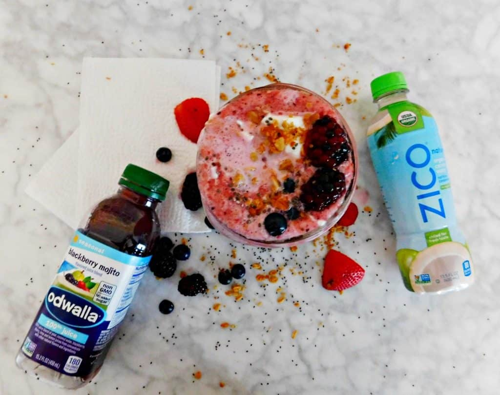 flay lay photo of smoothie recipe with greek yogurt, and bottled juice on marble table