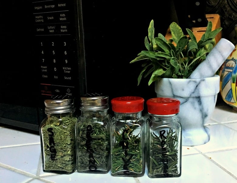 herbs in bottles in front of microwave