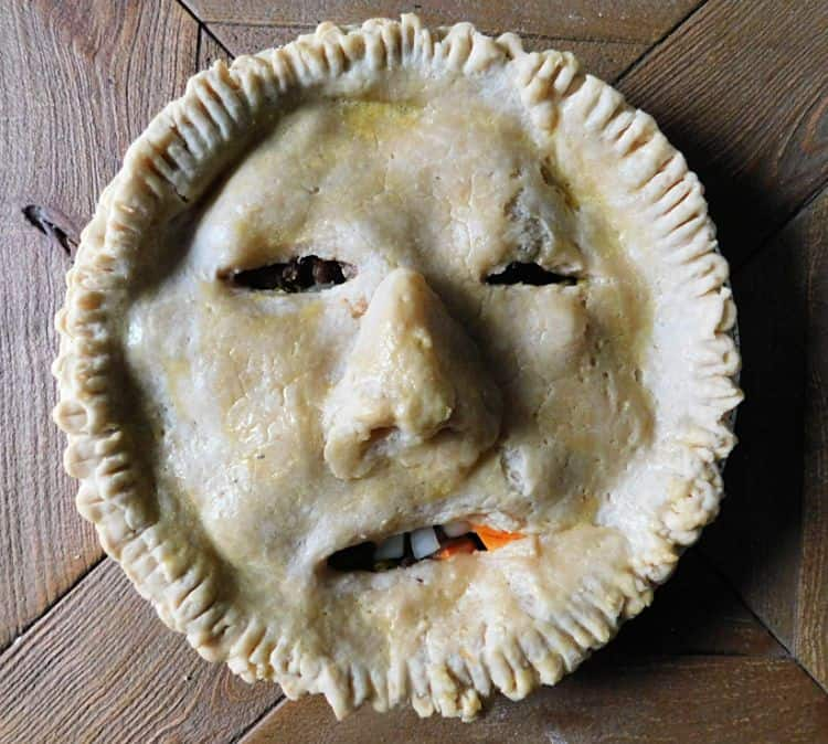 meat pie with slits cut into crust to make a face