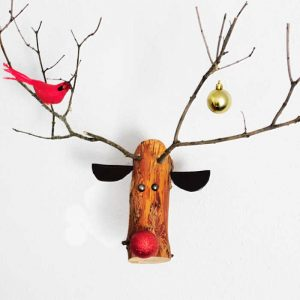 log reindeer hanging on while with bird and ornament on antlers