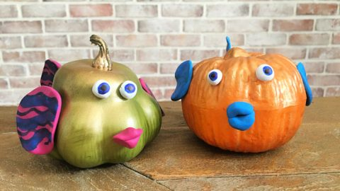 green and orange pumpkin fish with brick background behind it