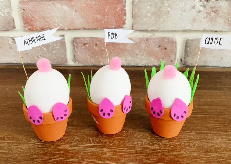 3 bunny pots with name tags in front of brick wall