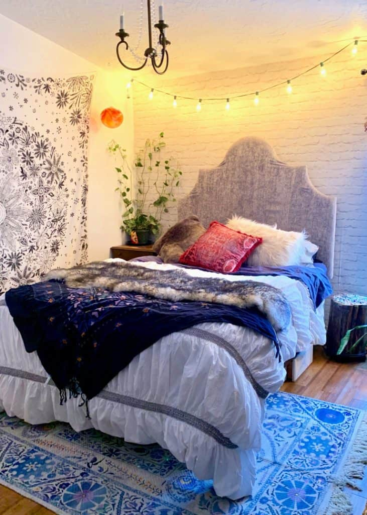 string lights above the bed in hygge bedroom