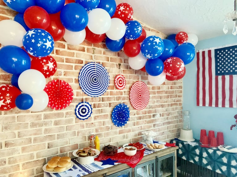 red white and blue balloons hung over a usa themed tablescape