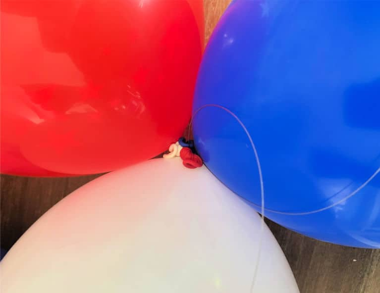 red white and blue balloons tied together