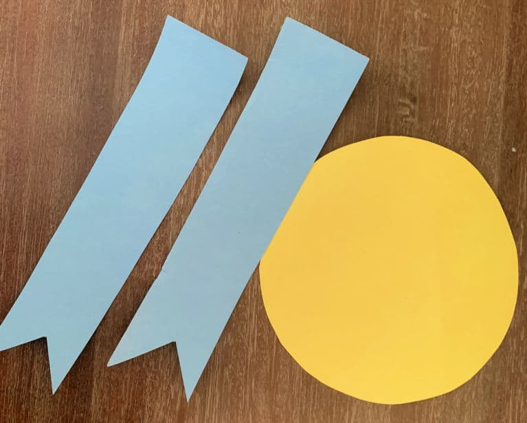 yellow circle and ribbons cut out of paper to make the paper plate awards.