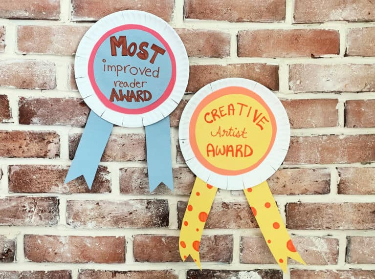 completed paper plate awards hanging on brick wall.