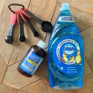 Dawn, castor oil and a measuring spoon on a table