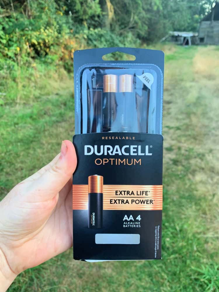hand holding duracell battery package in a field
