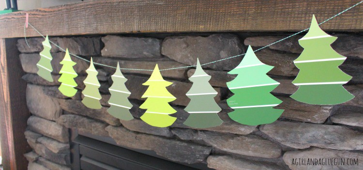 trees cut out of paint chips hanging from mantle