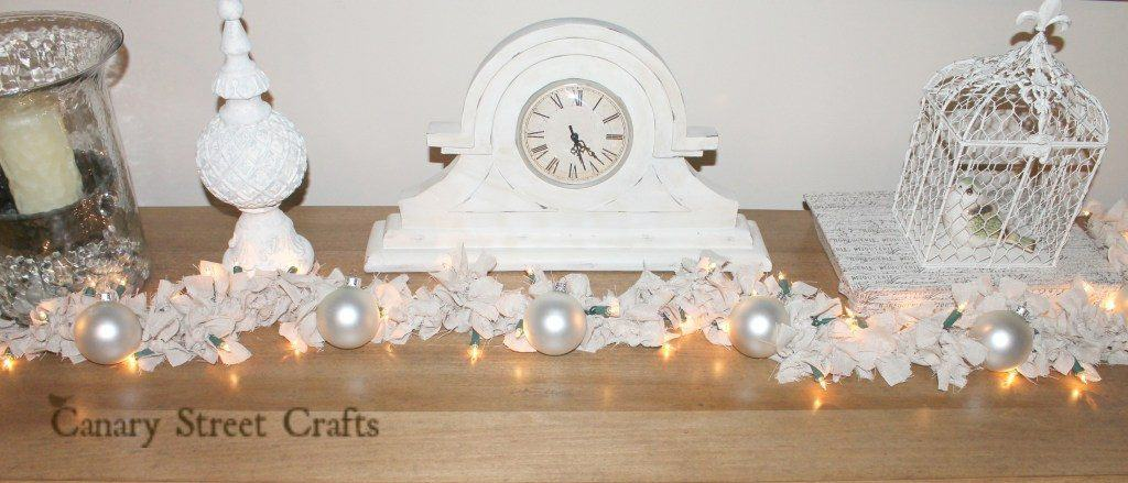 rag diy christmas garland on table in front of clock