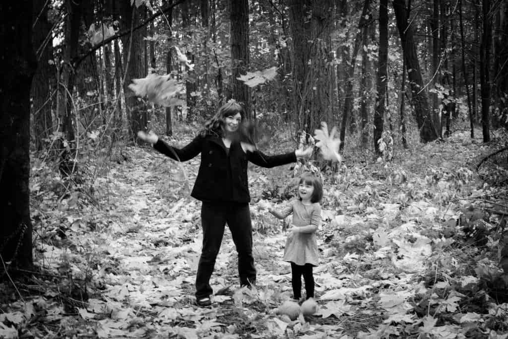 mother and daughter dancing in the leaves