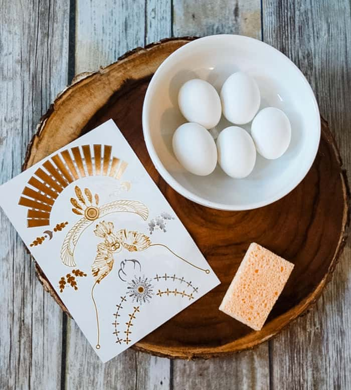 Materials for dyeing and tattooing eggs on a wood plate.