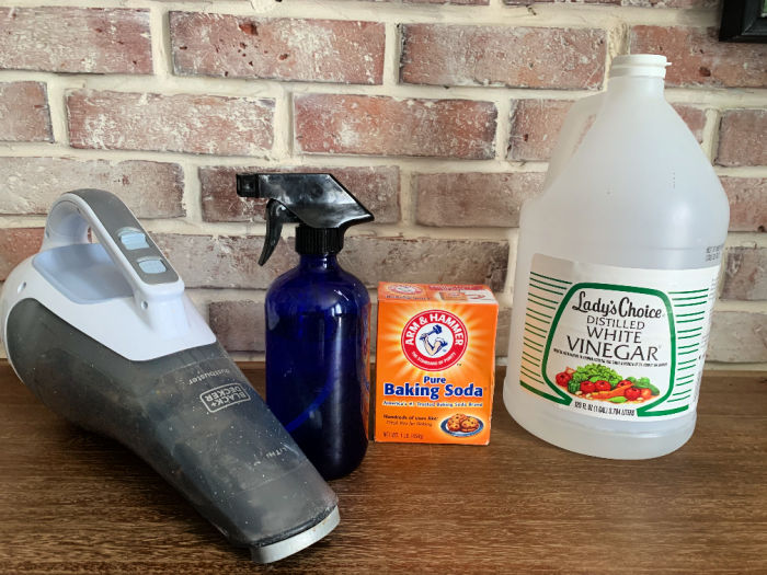 Supplies to clean a mattress: vinegar, baking soda, spray bottle and vacuum.